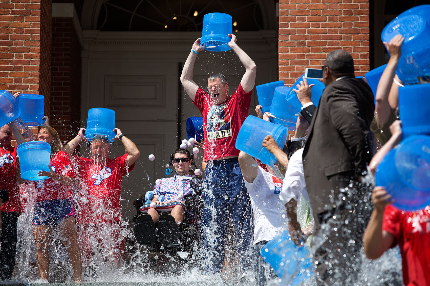 Gov. Charlie Baker and a crowd of people take the ALS Ice Bucket Challenge in 2015 as Pete Frates center looks on at the top of the State House steps