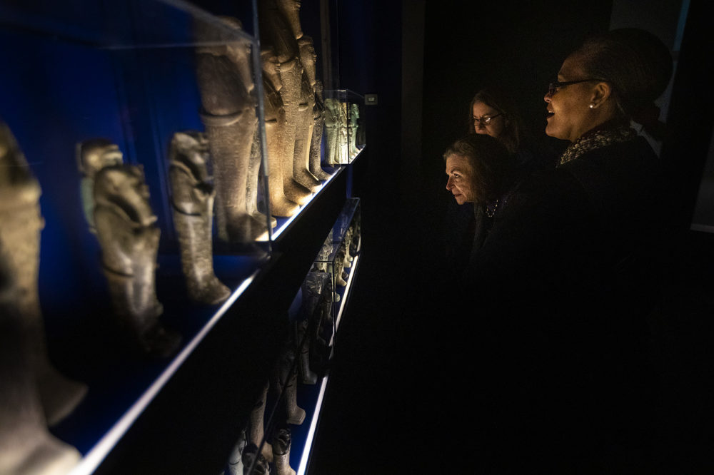 "Visitors to the MFA's Ancient Nubia Now exhibition look at funerary figurines known as ""shawabties."" These small sculptures were often buried with  Nubian kings and queens, numbering sometimes in the hundreds as guardian sentinels for the afterlife. (Jesse Costa/WBUR)"