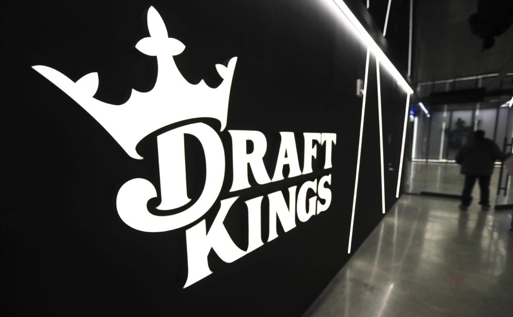 A worker passes logos at the DraftKings sports betting company headquarters in May in Boston. (Charles Krupa/AP)