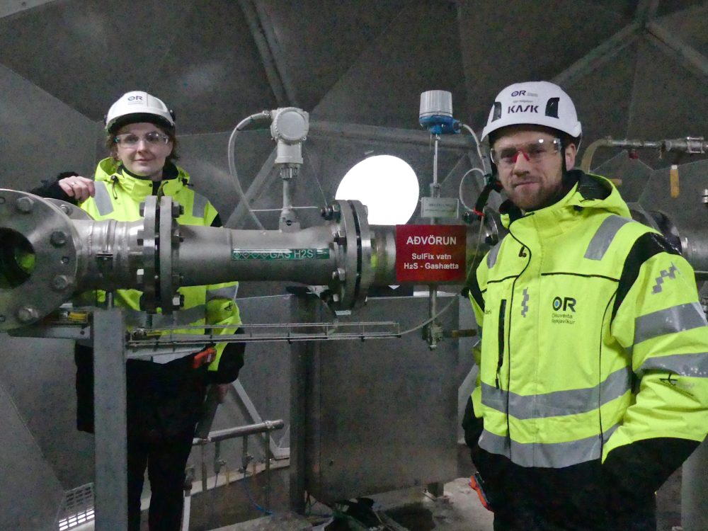 Sandra Ósk Snæbjörnsdóttir (left) and Kári Helgason at the injection well indoors. (Karyn Miller-Medzon/Here & Now)