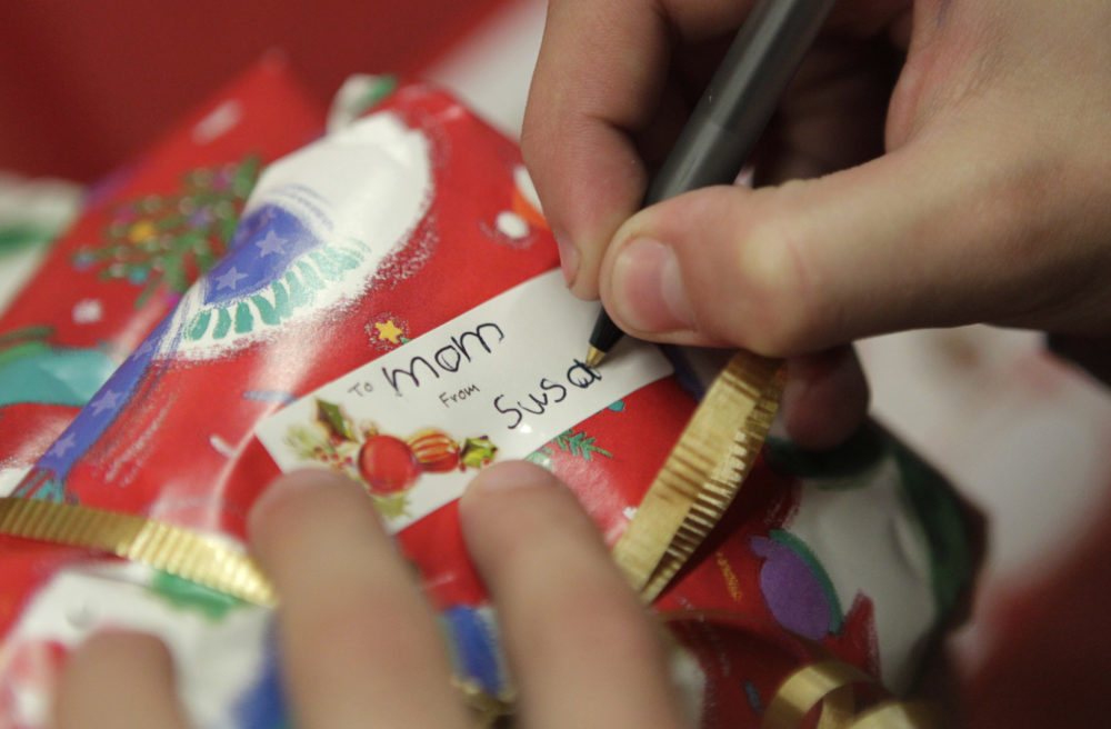 In this Dec. 17, 2010 photo, a young girl writes a gift tag for her mother. (Jae C. Hong/AP)