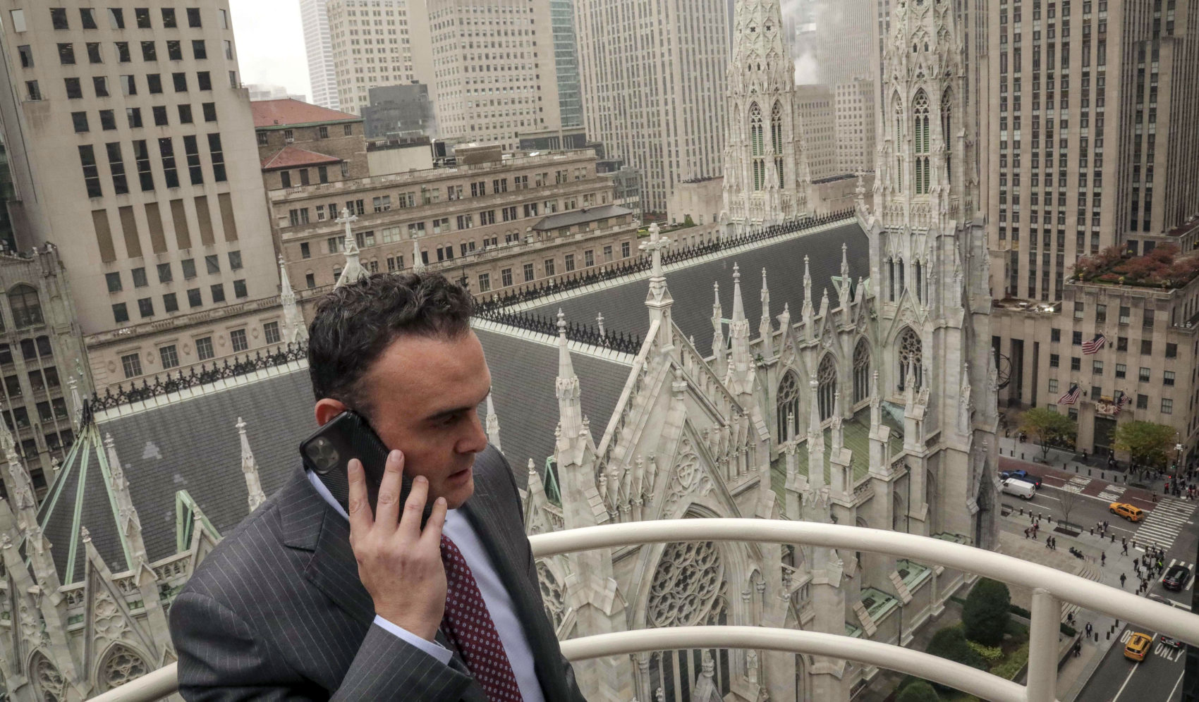Attorney Adam Slater takes a phone call on a patio outside his high-rise Manhattan office overlooking St. Patrick's Cathedral, in New York. Slater's firm is representing clients accusing the Roman Catholic Church of sexual abuse. (Bebeto Matthews/AP)