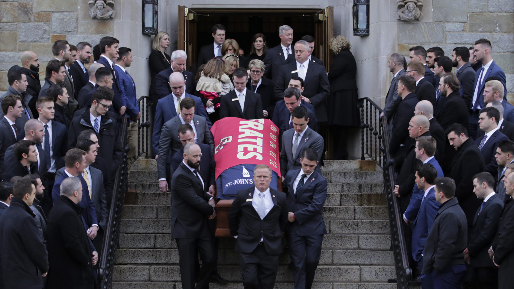 Boston College athletes, from past and present teams, watch as the casket is carried from the funeral of Pete Frates at St. Ignatius of Loyola Parish in Chestnut Hill. (Charles Krupa/AP)