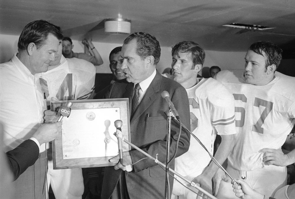 President Richard Nixon presents a plaque to Texas football coach Darrell Royal, naming the Longhorns the No. 1 college football team in college football's 100th year, Dec. 6, 1969.  At right is Texas quarterback James Street.  (AP Photo)