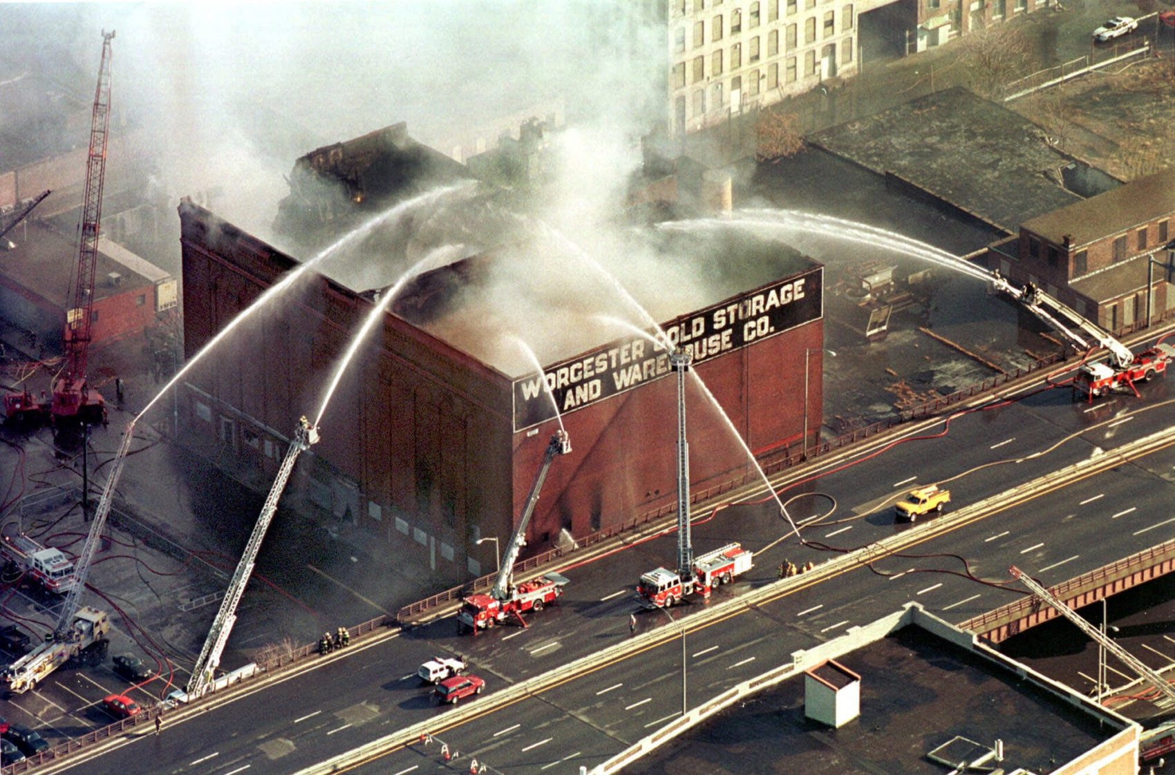 In this 1999 photo, firefighters spray water onto the burning Worcester Cold Storage and Warehouse Co. building, where six Worcester firefighters lost their lives. (Paul Connors/AP)