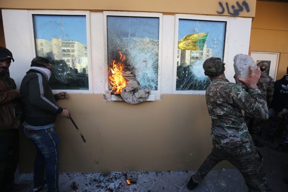 Members the Hashed al-Shaabi, a mostly Shiite network of local armed groups trained and armed by powerful neighbour Iran, smash the bullet-proof glass of the US embassy's windows in Baghdad. (Photo by Ahmad Al-Rubaye/AFP via Getty Images)