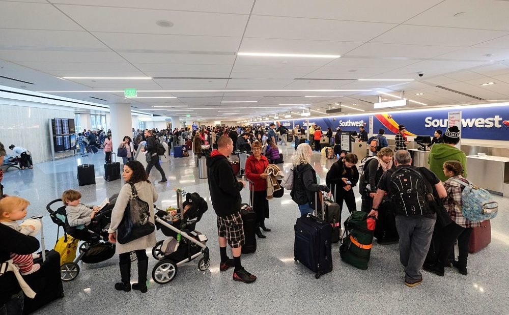 Holiday travelers crowd check in before departure. (Ringo Chiu/AFP via Getty Images)