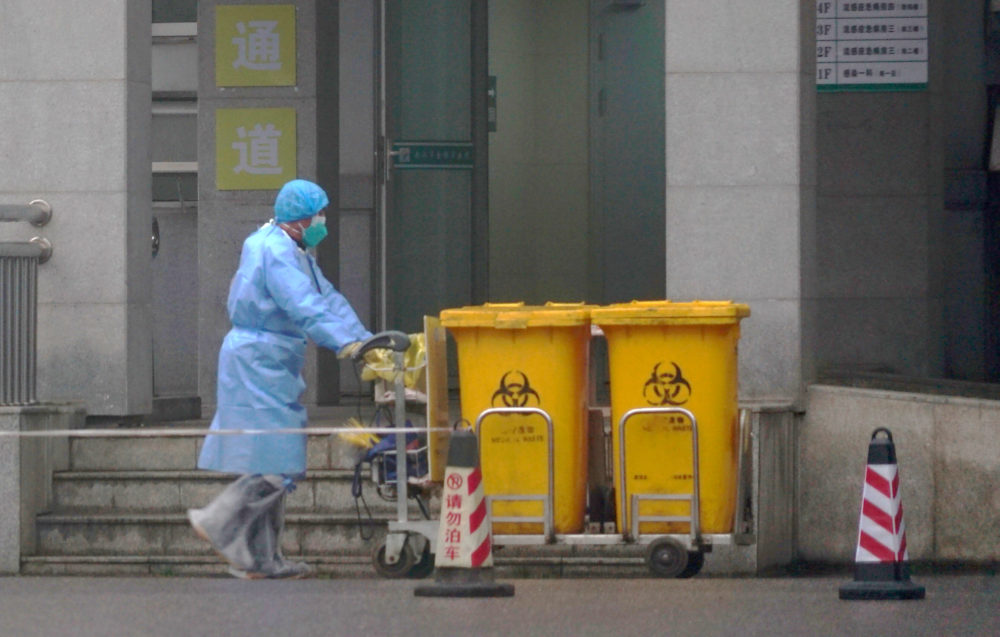 Staff move bio-waste containers past the entrance of the Wuhan Medical Treatment Center, where some infected with a new virus are being treated, in Wuhan, China on Jan. 22. (Dake Kang/AP)