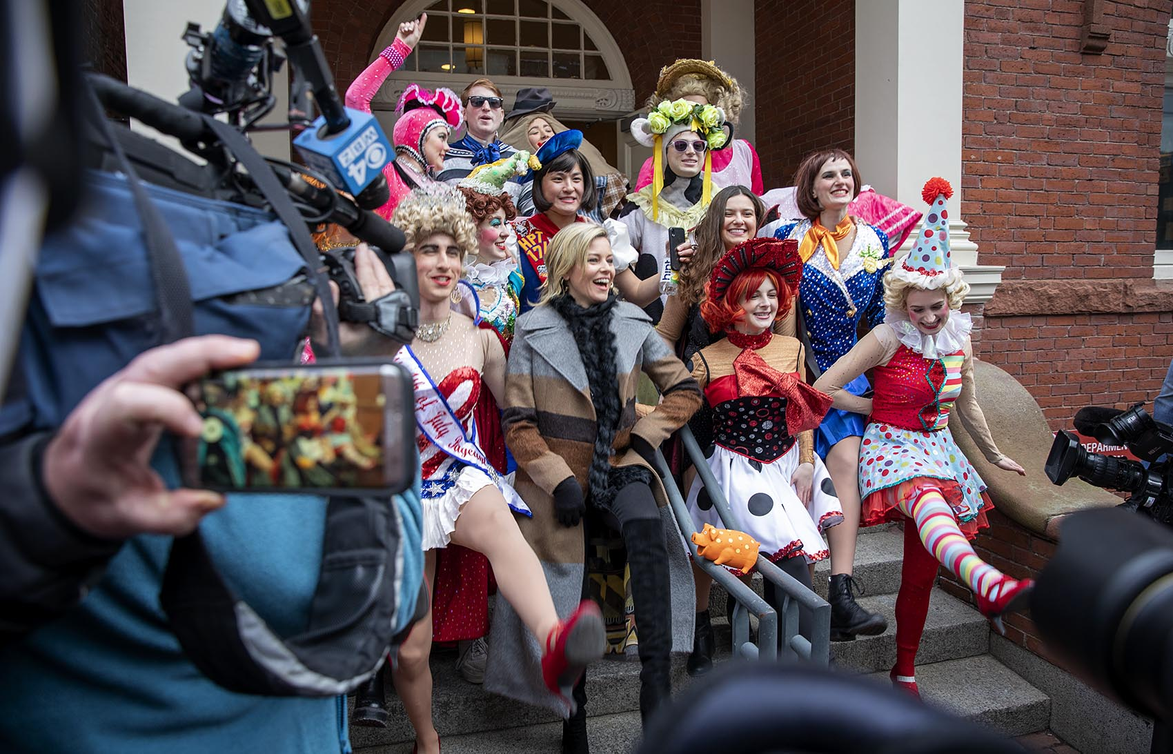 Elizabeth Banks, Hasty Pudding Theatricals' 2020 Woman of the Year, lines up with Hasty Pudding actors for a photo on the steps of Farkas Hall. (Robin Lubbock/WBUR)