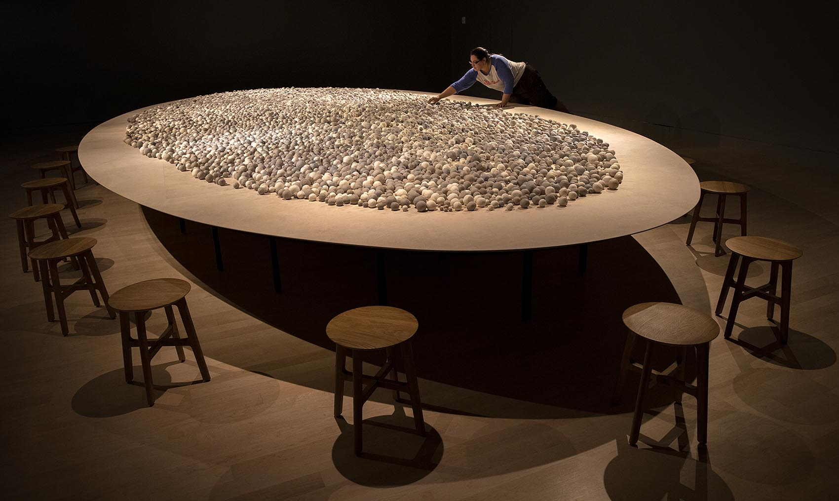 """A visitor places a clay sphere into """"Archive of Mind."""" (Robin Lubbock/WBUR)"""