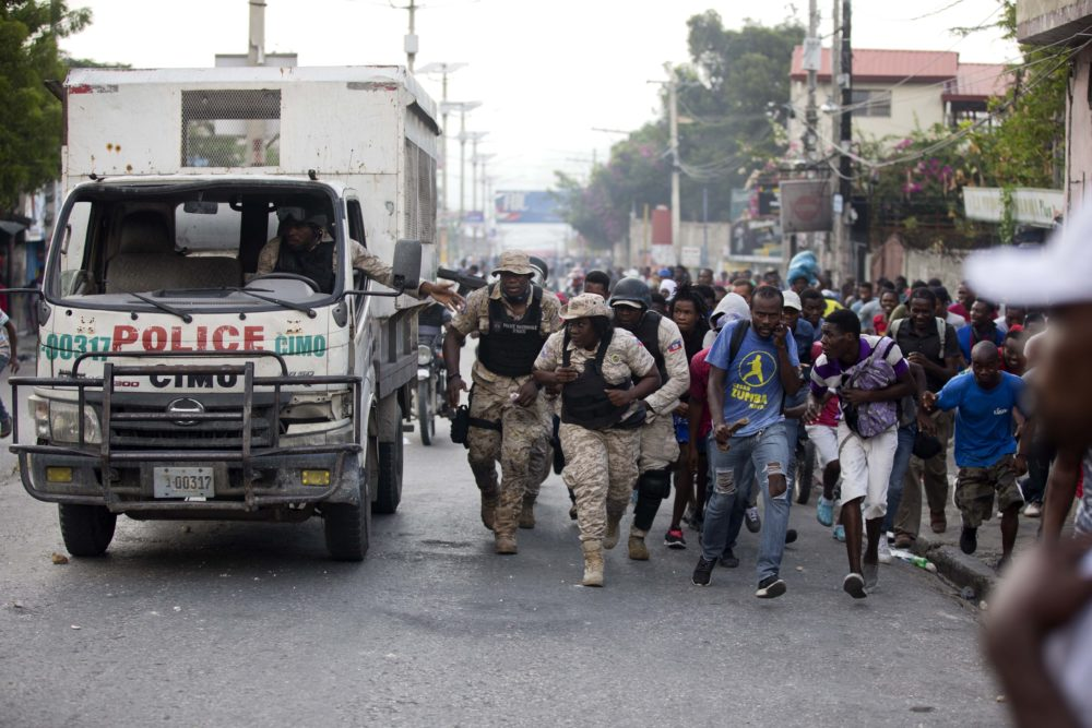 Police officers and protesters take cover behind a police truck as shots ring out during a protest to demand the resignation of Haiti's president Jovenel Moise in Port-au-Prince, Haiti, in November (Dieu Nalio Chery/AP)