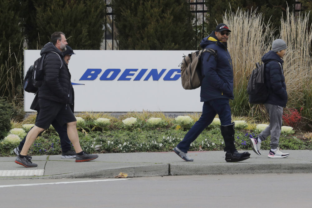 Workers walk past a Boeing Co. sign as they leave the factory where the company's 737 Max airplanes are built, Dec. 17, 2019. As Boeing prepares to shutter much of the huge factory near Seattle that builds the grounded 737 Max jet, the economic hit is reverberating across the United States. (Ted S. Warren/AP)