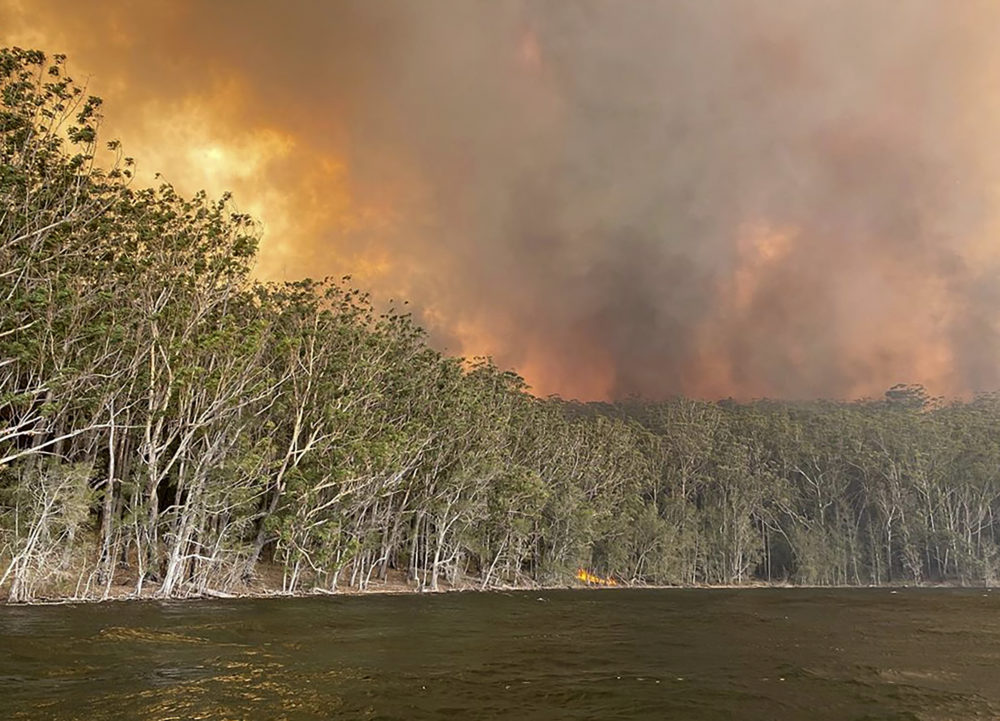 Smoke and wildfire rage behind Lake Conjola, Australia, Thursday, Jan. 2, 2020. (Robert Oerlemans via AP)