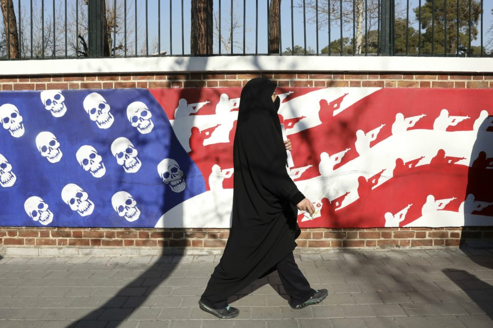 A mourner walk back from a funeral ceremony for Iranian Gen. Qassem Soleimani and his comrades, who were killed in Iraq in a U.S. drone attack on Friday, passing graffiti on the wall of the former U.S. Embassy in Tehran, Iran, Monday, Jan. 6, 2020. Funeral ceremonies for Soleimani drew a crowd said by police to be in the millions, on Monday in Tehran, where his replacement vowed to take revenge. (Vahid Salemi/AP)