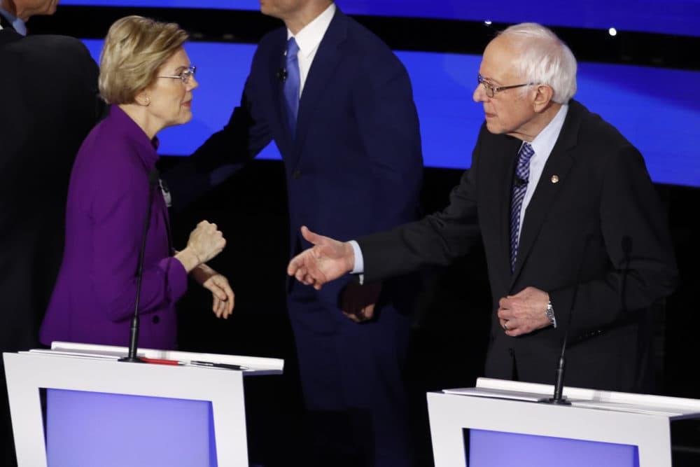 Democratic presidential candidate Sen. Elizabeth Warren, D-Mass., left and Sen. Bernie Sanders, I-Vt. talk Tuesday after a Democratic presidential primary debate hosted by CNN and the Des Moines Register. (Patrick Semansky/AP)