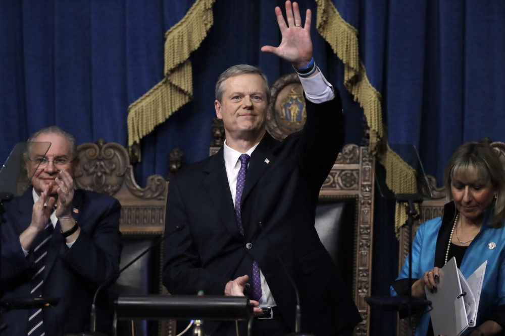 Massachusetts Gov. Charlie Baker, center, waves at the conclusion of his state of the state address in the House Chamber as Speaker of the House Robert DeLeo, behind left, and Senate President Karen Spilka, right, look on, Tuesday, at the State House. (Steven Senne/AP)