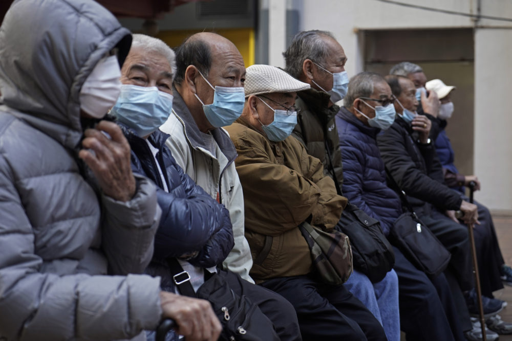 Elderly men sit at a park wearing face masks in Hong Kong, Thursday, Jan. 30, 2020. (Kin Cheung/AP)