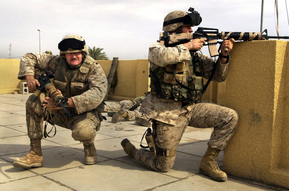 In this Sunday, Oct. 31, 2004 file photo, U.S. Marine snipers from the 2nd Battalion, 5th Marine Regiment, take cover during a gun battle with insurgents in Ramadi in Anbar province, Iraq. (Jim MacMillan/AP)