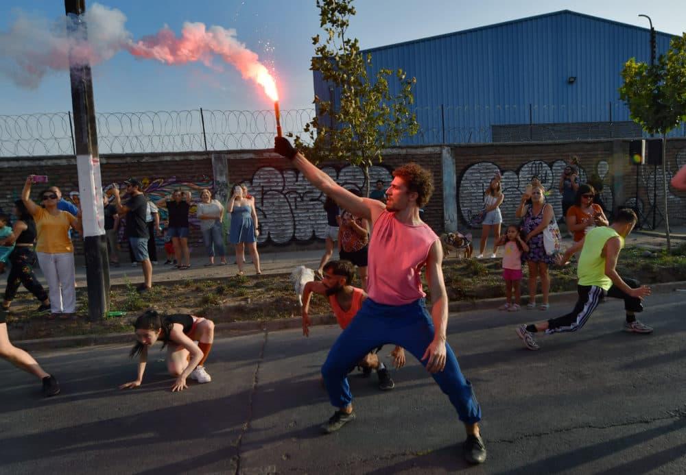 """A dancer raises a flare during a performance of José Vidal's """"Emerger."""" (Jorge Sanchez for WBUR)"""