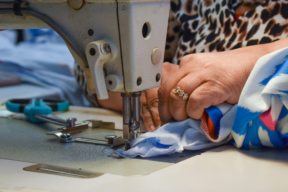 A seamstress works on an industrial sewing machine at a clothing factory in Fall River, Massachusetts. (Allison Hagan/Here & Now)