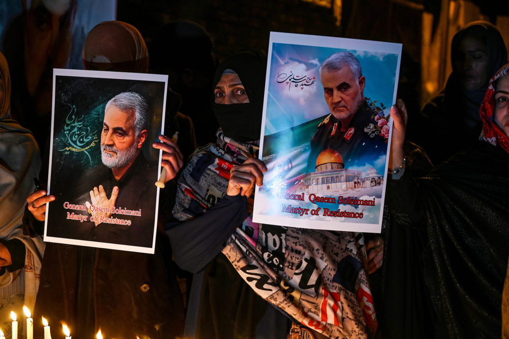 Shiite Muslims hold pictures of slain top Iranian general Qasem Soleimani to pay him tribute during a candle light vigil in IslamabadJanuary 8, 2020. (Aamir Qureshi/AFP via Getty Images)