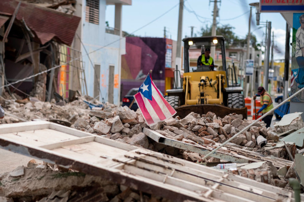 A Puerto Rican flag waves on top of a pile of rubble as debris is removed from a main road in Guanica, Puerto Rico on January 8, 2020, one day after the earthquake. (Ricardo Arduengo/AFP/Getty Images)