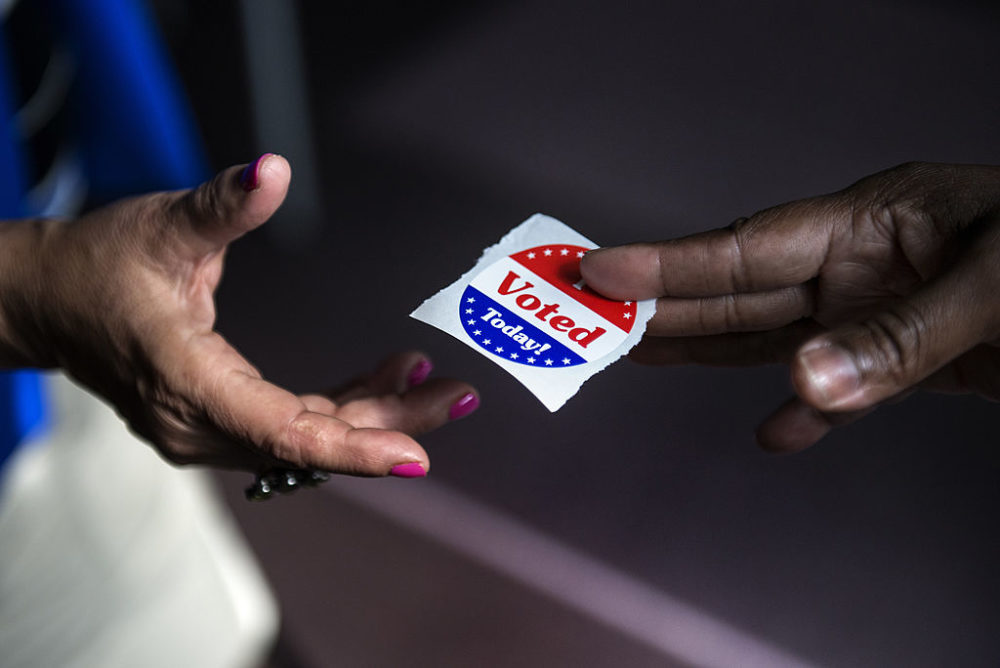"""A poll worker hands out """"I Voted Today"""" stickers. (Brendan Smialowski/AFP/Getty Images)"""