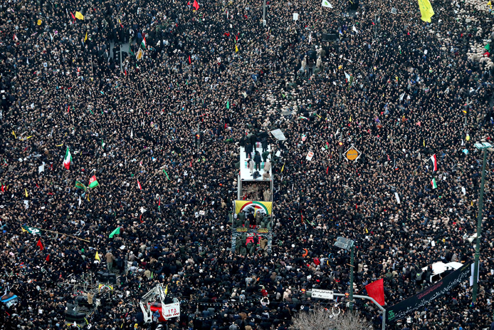 Coffins of Gen. Qassem Soleimani and his comrades who were killed in Iraq by a U.S. drone strike, are carried on a truck surrounded by mourners during a funeral procession, in the city of Mashhad, Iran, Sunday, Jan. 5, 2020. (Mohammad Hossein Thaghi/Tasnim News Agency via AP)
