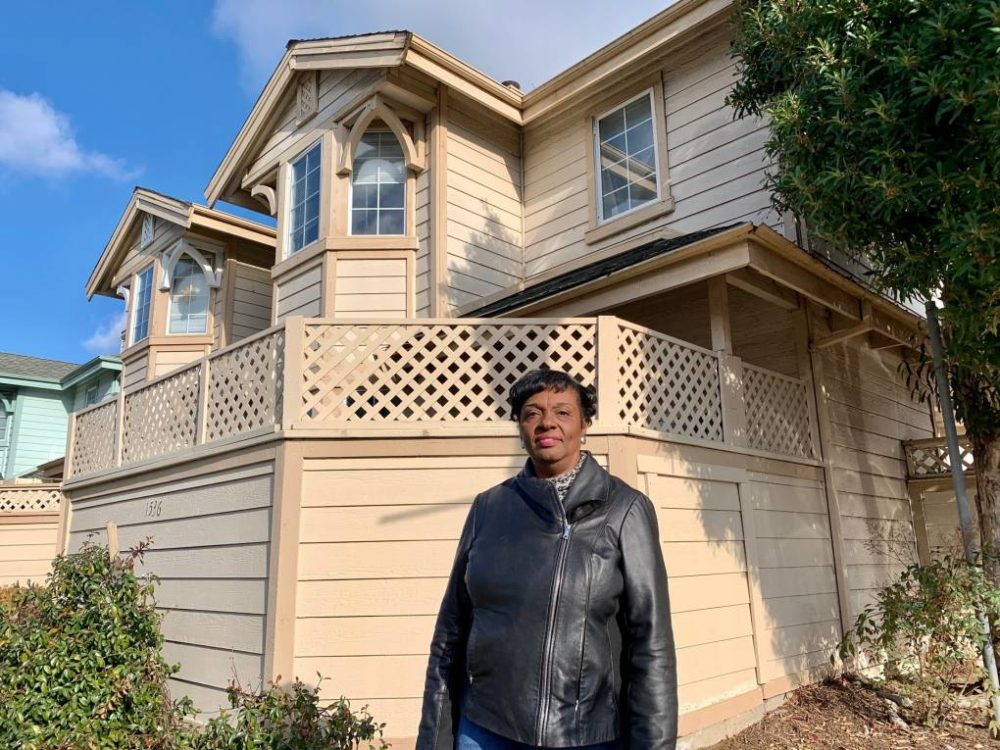 Gayla Newsome stands in front of her Oakland home. (Molly Solomon/KQED)