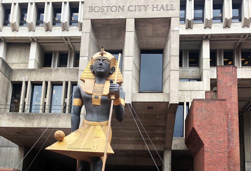 """A 25-foot, 2-ton recreation of an Egyptian tomb guard arrived in City Hall Plaza Tuesday. It signaled the summer arrival of a large exhibition of Egyptian artifacts called """"King Tut: Treasures of the Golden Pharaoh."""" (Christian Burno/WBUR)"""