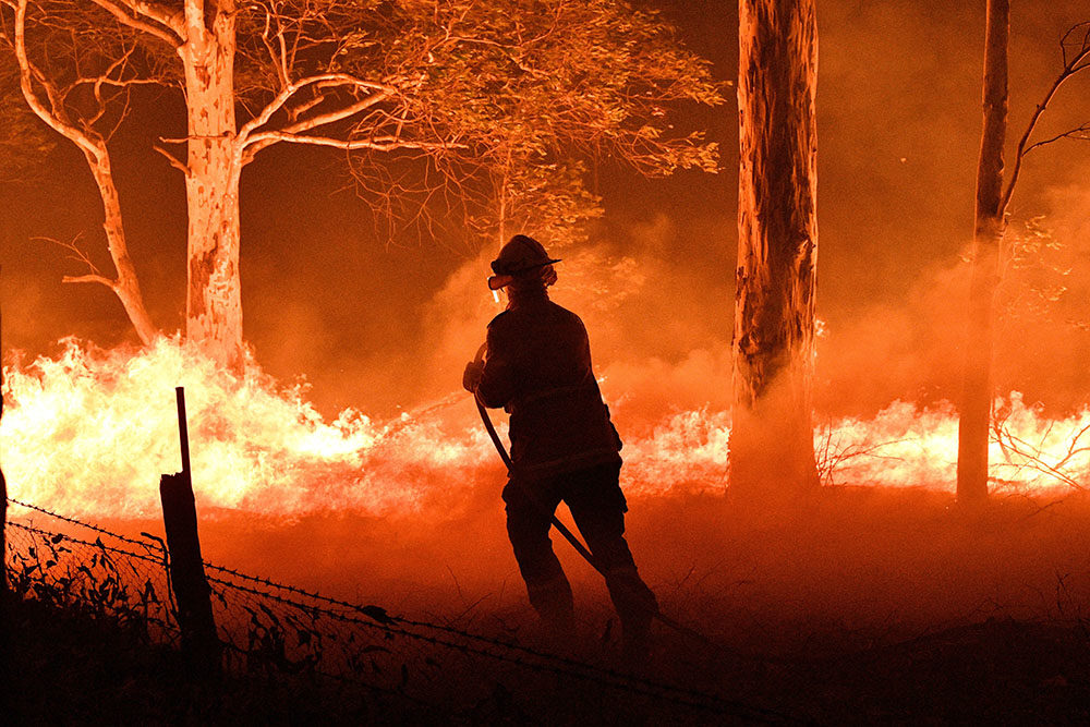 This picture taken on December 31, 2019 shows a firefighter hosing down trees and flying embers in an effort to secure nearby houses from bushfires near the town of Nowra in the Australian state of New South Wales. (SAEED KHAN/AFP via Getty Images)