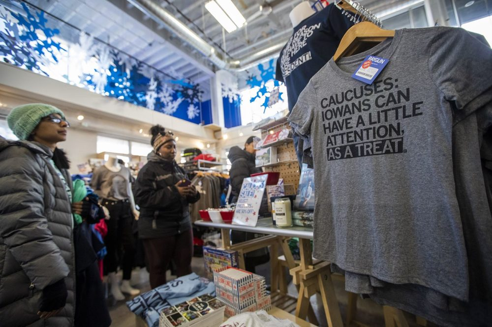 Shoppers at RAYGUN in Des Moines peruse the selection of printed t-shirts and other items with various quips about the Iowa caucus. (Jesse Costa/WBUR)