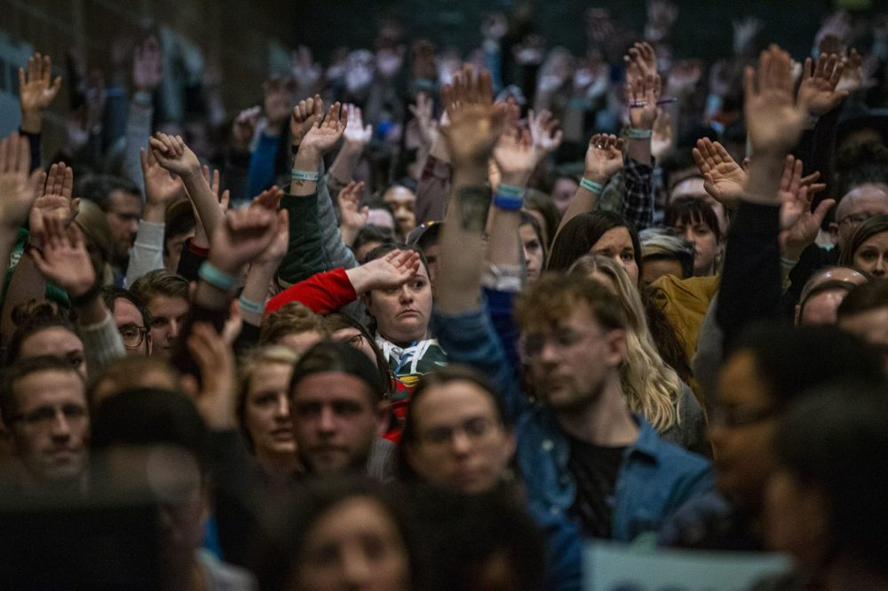 Caucus participants at Central Campus High School raise their hands to be counted, Feb, 3, 2020. (Jesse Costa/WBUR)