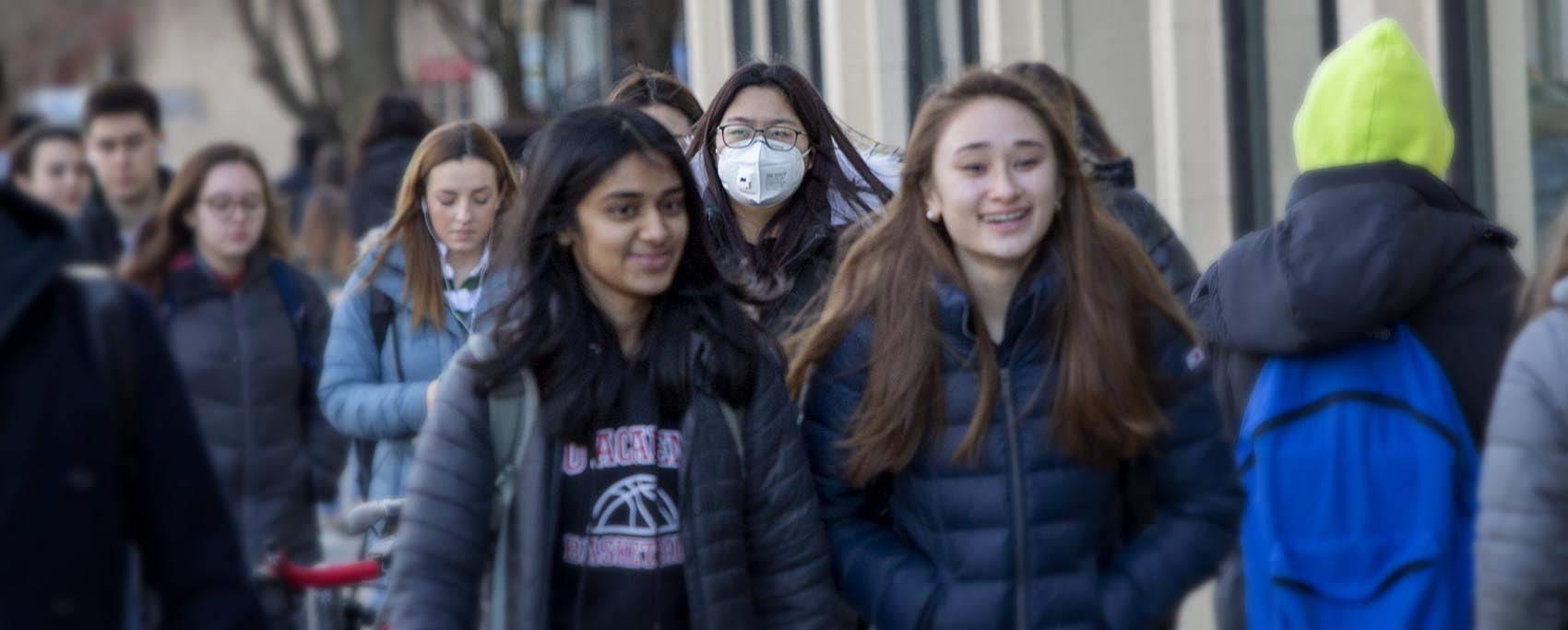 A woman wears a mask as she walks along on a busy Boston sidewalk. (Robin Lubbock/WBUR)