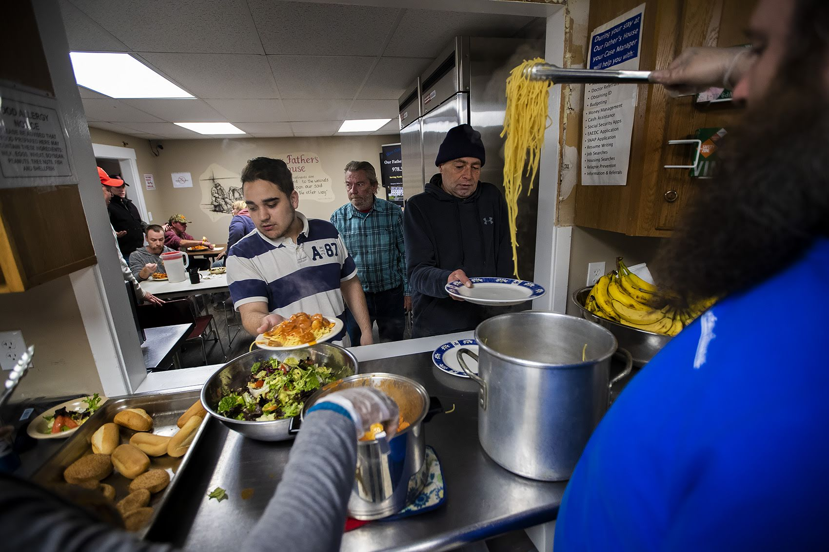 Guests recieve a spaghetti dinner at Our Father's House in Fitchburg. (Jesse Costa/WBUR)