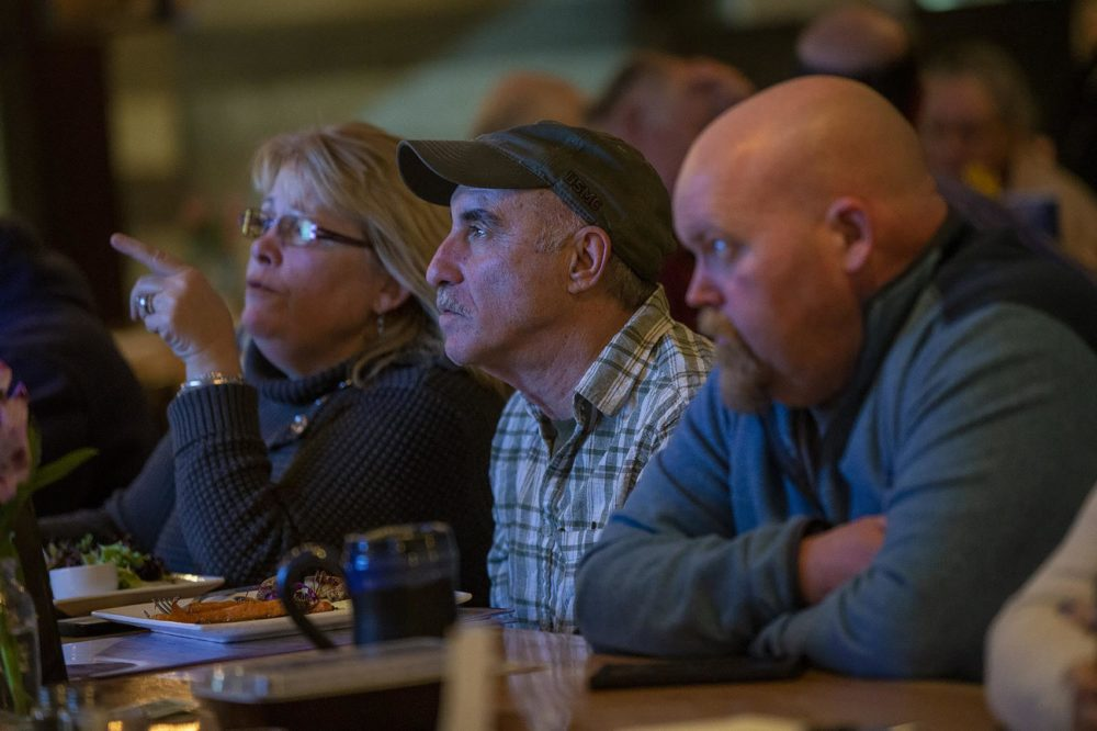 (L-R) Terry Dwyer, her husband Bob Trott, and Dennis Roberts sit at the bar at Revolution TapRoom and Grill in Rochester, NH. (Jesse Costa/WBUR)