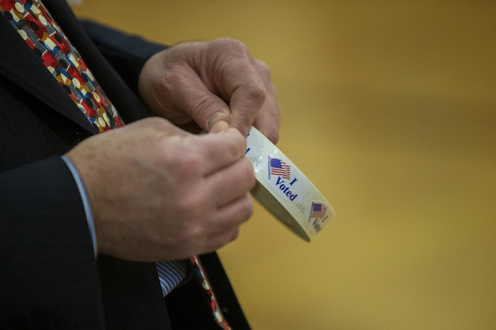 "William Tucker passes out ""I Voted"" stickers after people finish voting at Portsmouth Middle School. (Jesse Costa/WBUR)"