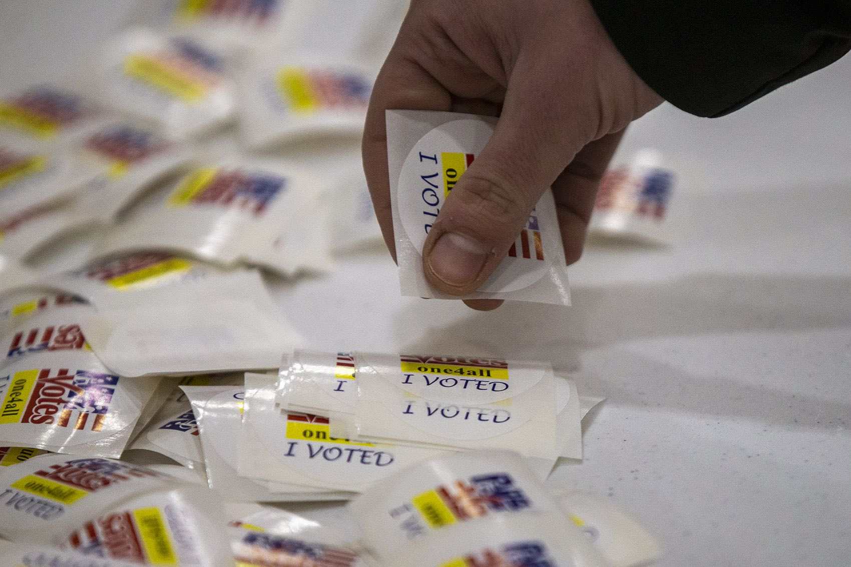"""A voter picks up an """"I Voted"""" sticker after going to the polls at Oyster River High School in Durham, N.H. (Jesse Costa/WBUR)"""
