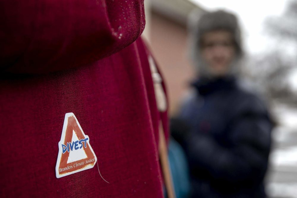 "A protester wore a ""Divest"" sticker at a Brandeis Climate Justice demonstration at the university in February. (Robin Lubbock/WBUR)"