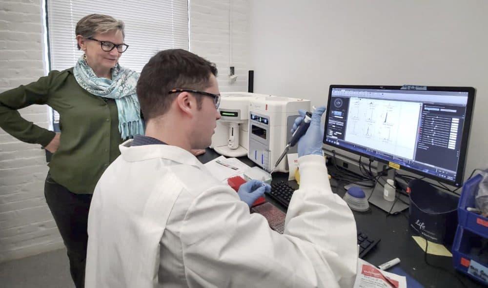 Anne De Groot speaking with a lab scientist at EpiVax. (Angus Chen/WBUR)