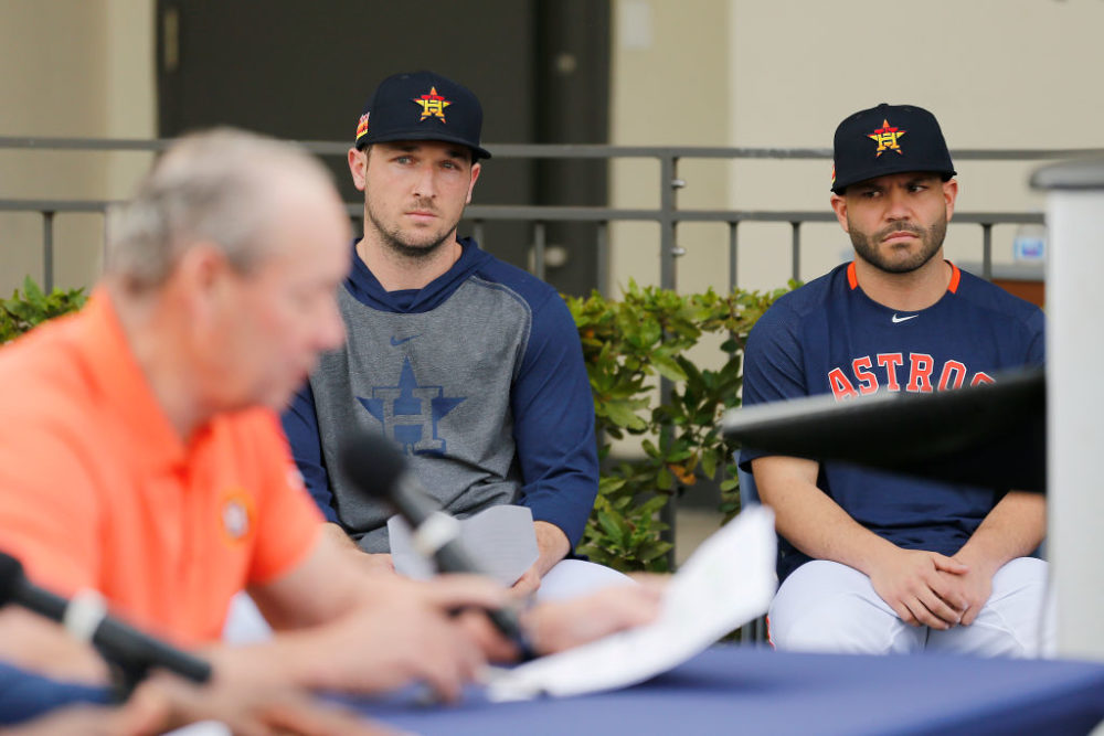 Alex Bregman and Jose Altuve of the Houston Astros look on as owner Jim Crane reads a prepared statement during a press conference on Thursday. (Michael Reaves/Getty Images)