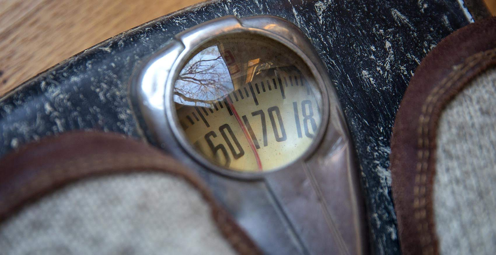 A person stands on an old body weight scale. (Robin Lubbock/WBUR)