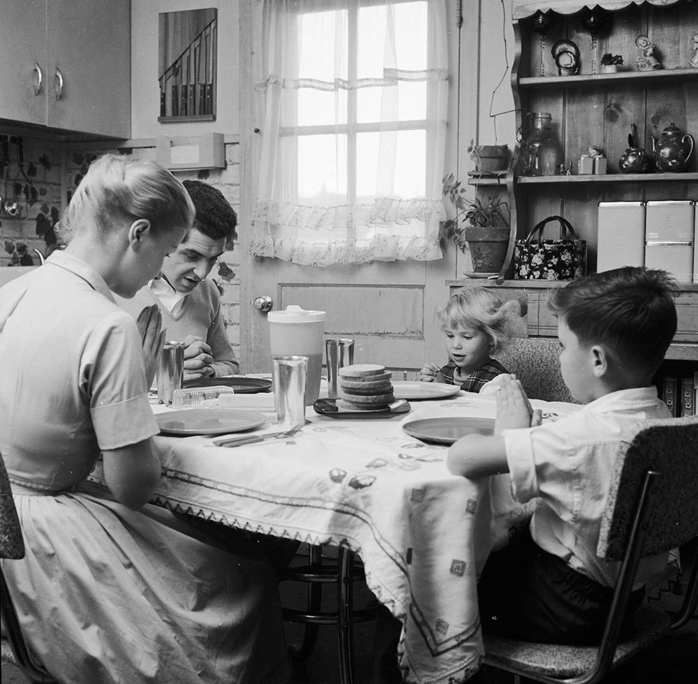 Mr. and Mrs. Paul, and their children Belinda and Cliff, say grace before starting their meal.  (Jacobsen /Three Lions/Getty Images)