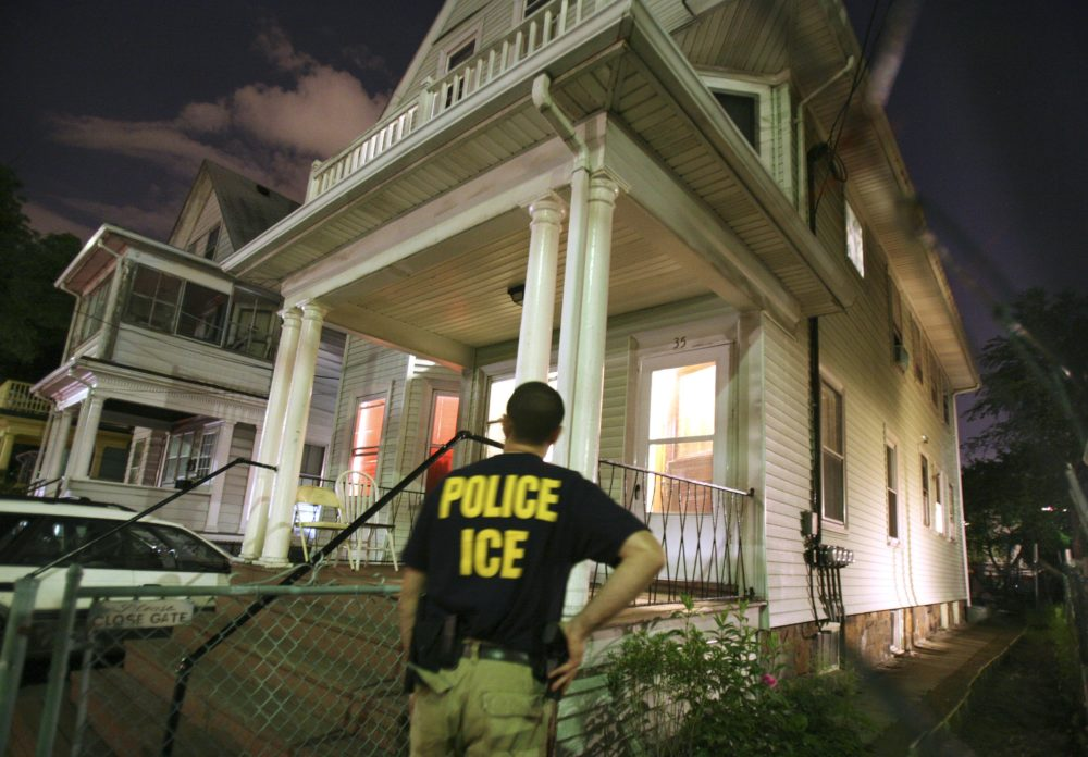 In this file photo, an agent from the Immigration and Customs Enforcement agency keeps watch at the side of a house while other agents from ICE are inside in search of a suspect. (Michael Dwyer/AP)