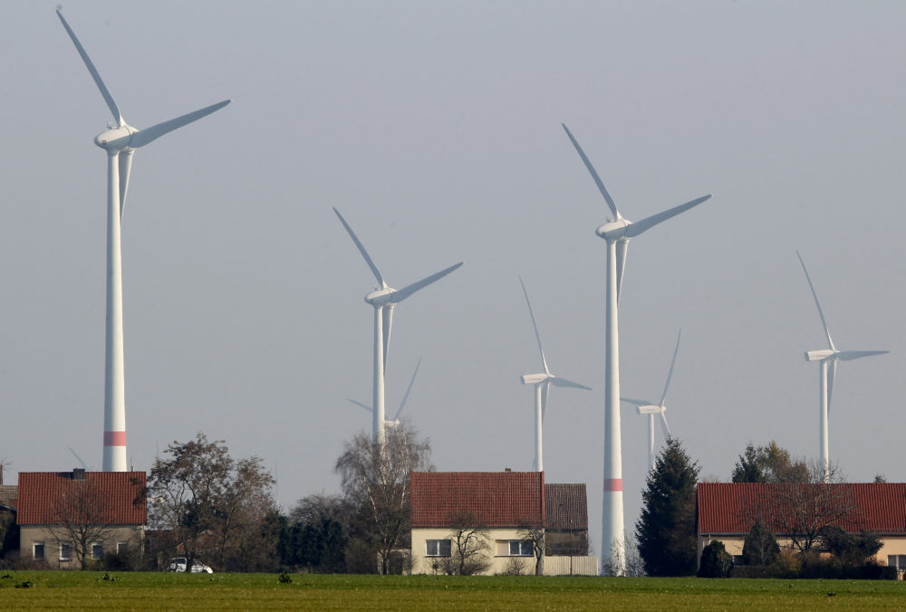 Wind turbines stand behind houses of the village of Feldheim near Berlin, Germany. (Michael Sohn/AP)