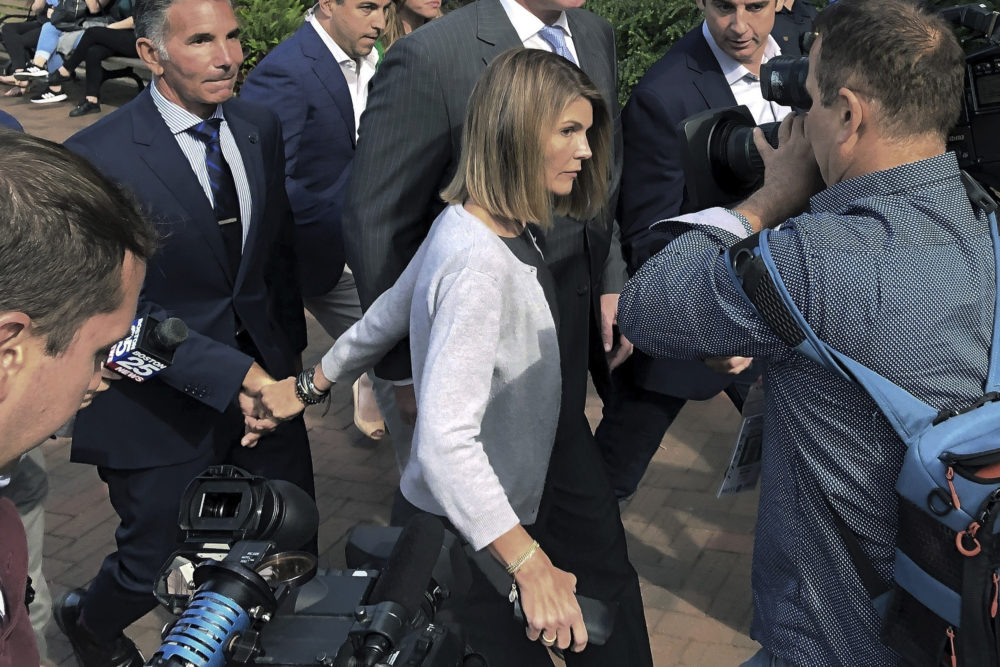 On Aug. 27, 2019, actress Lori Loughlin departs hand in hand with her husband, clothing designer Mossimo Giannulli, left, in Boston, after a hearing in federal court in a nationwide college admissions bribery scandal. (Philip Marcelo/AP File Photo)