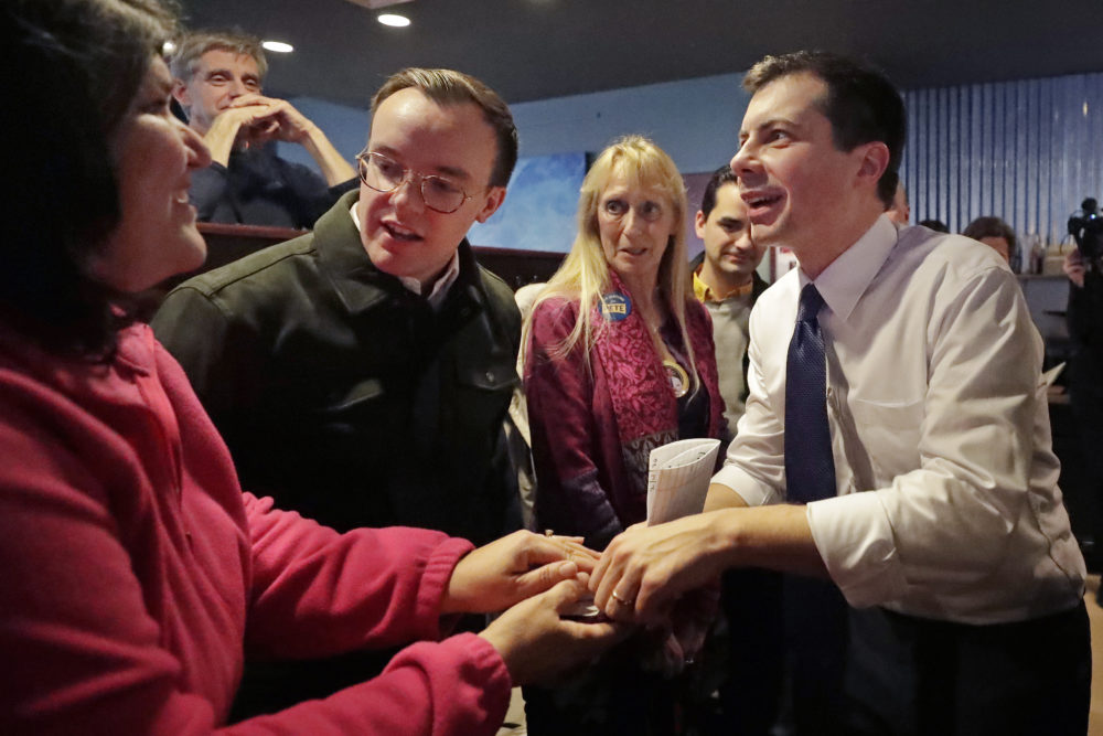 Democratic presidential candidate former South Bend Mayor Pete Buttigieg, right, and his husband, Chasten Buttigieg, left, greet people at a campaign event Tuesday in Hampton, N.H. (Elise Amendola/AP)