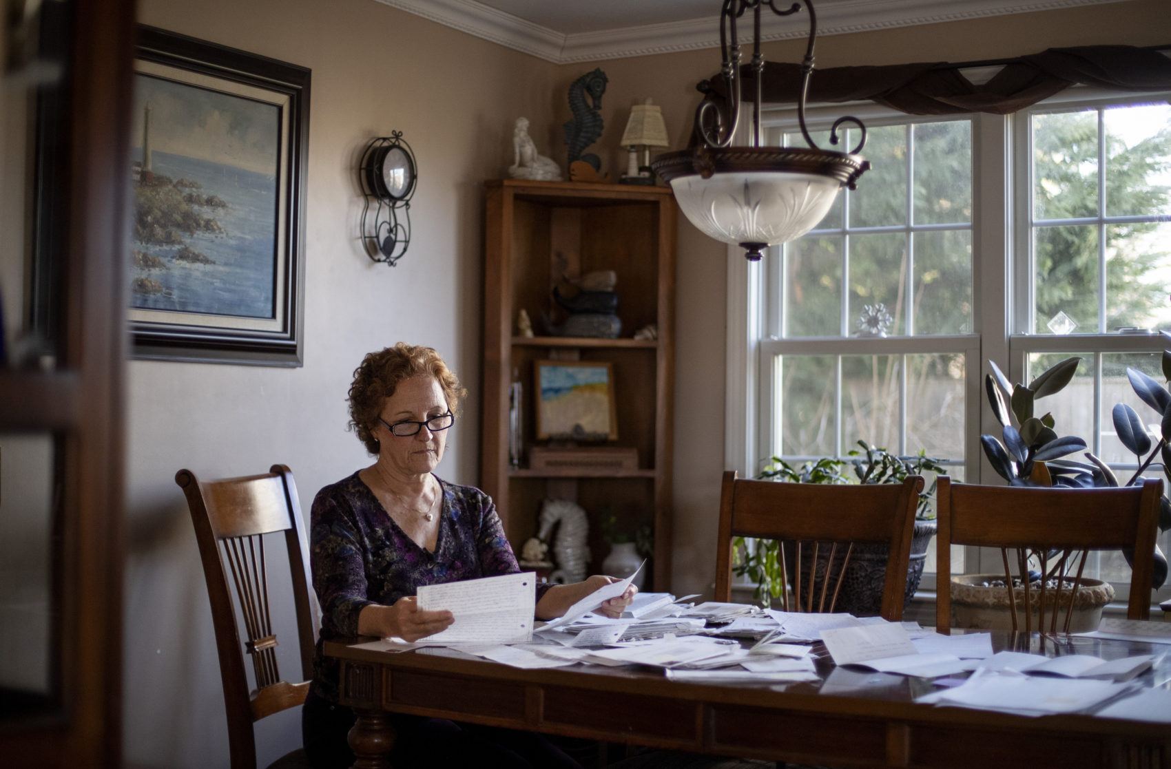 "Janet Uhlar sits at her dining room table with letters and photos she received through her correspondence with imprisoned Boston organized crime boss James ""Whitey"" Bulger, Jan. 31, 2020, in Eastham, Mass. (David Goldman/AP)"