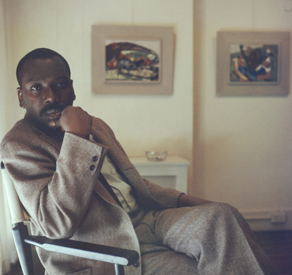Artist Jacob Lawrence sitting in front of some of his paintings. (Courtesy Robert W. Kelley/The LIFE Picture Collection via Getty Images)