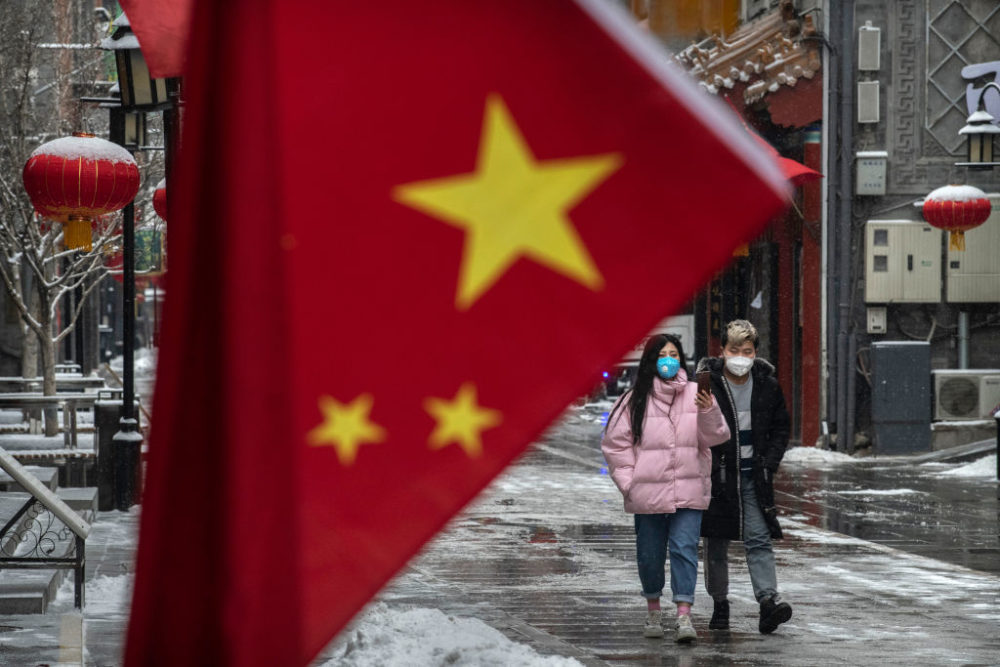 A Chinese couple wear protective masks as they walk during a snowfall in an empty and shuttered commercial street on February 5, 2020 in Beijing, China. (Kevin Frayer/Getty Images)